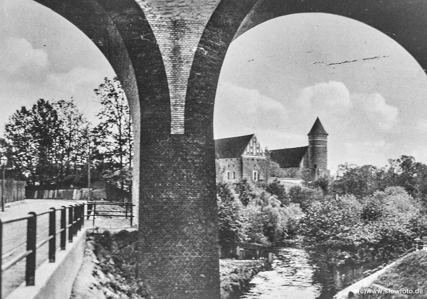 Blick auf das Schloss durch einen Bahnviadukt, der Fluss rechts ist die Alle